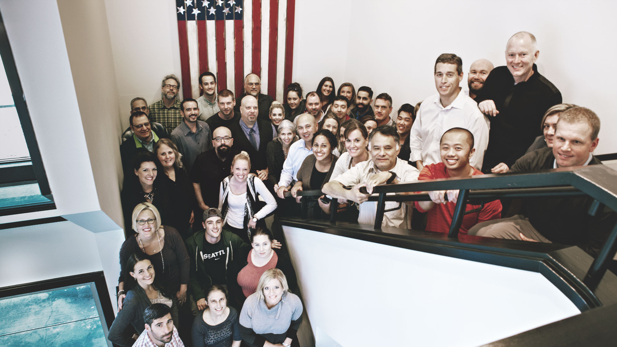 Launch employees standing in front of the American flag displayed in the Launch office