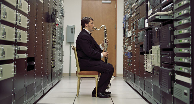 Man playing bass clarinet in server room