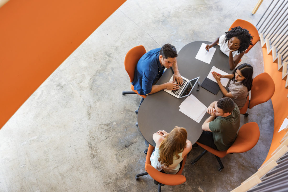 Top down view of a group of young entrepreneurs working together in a start up business meeting